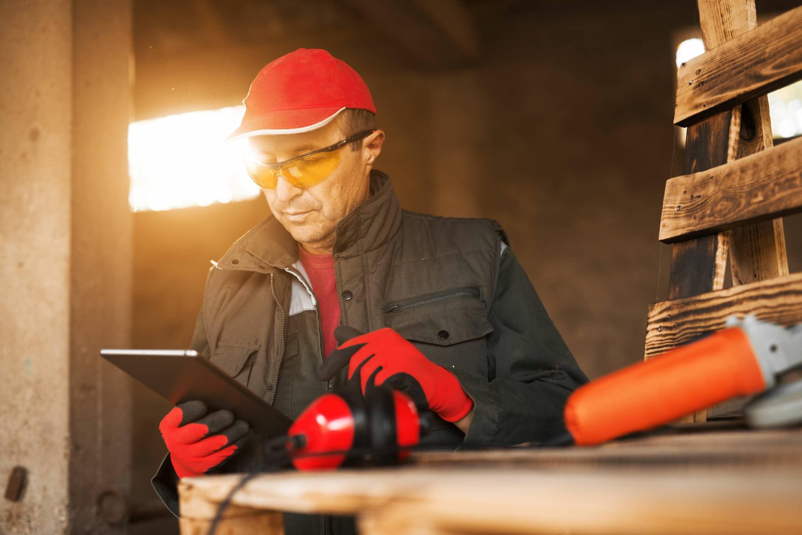 Handwerker mit Tablet Schutzbrille Werkzeug